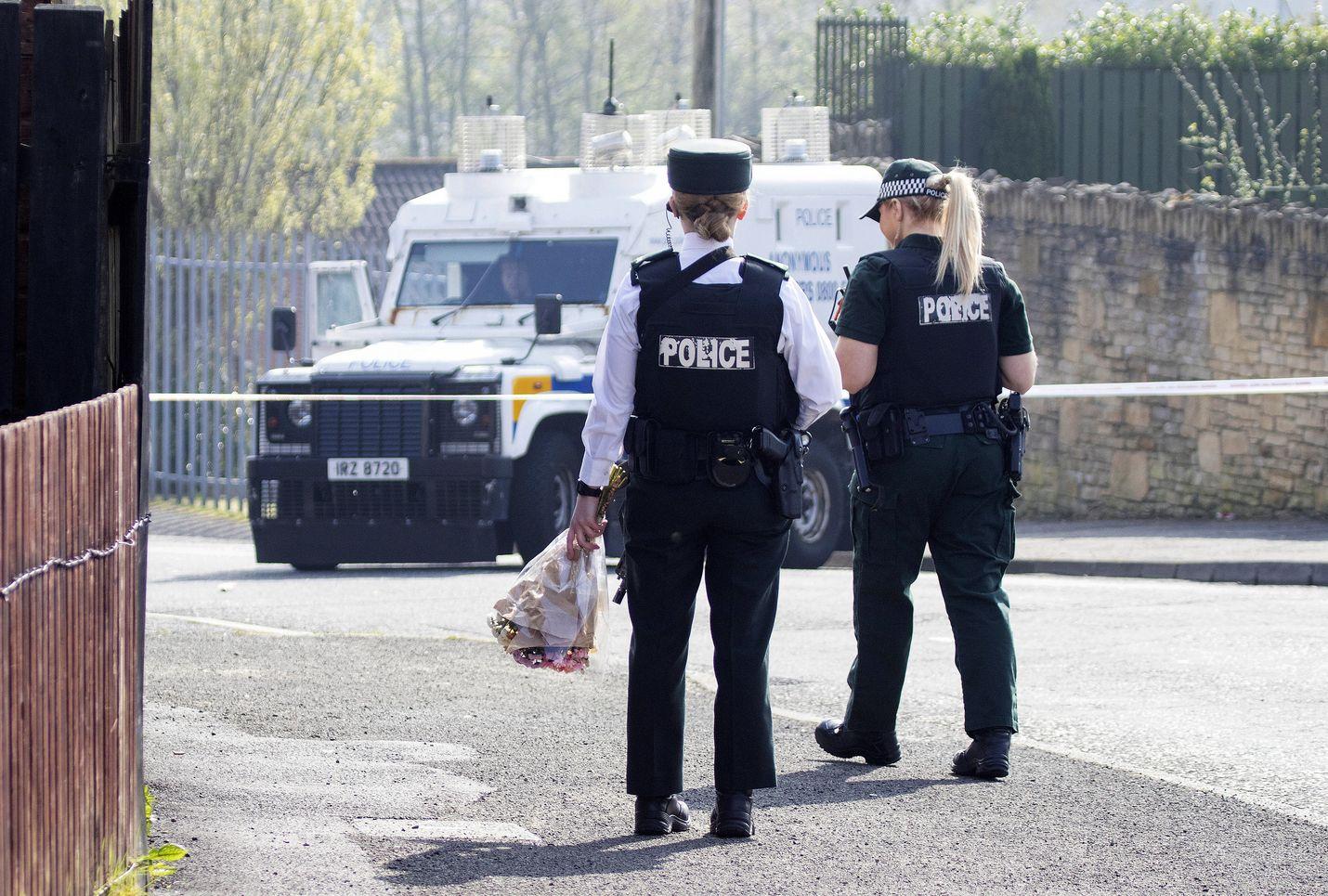 Poliisit veivät kukkia paikalle, jossa 29-vuotias toimittaja kuoli Londonderryn kaupungissa Pohjois-Irlannissa myöhään torstai-iltana. Ampujiksi epäillään yhtenäistä Irlantia ajavaa ääriryhmittymää.