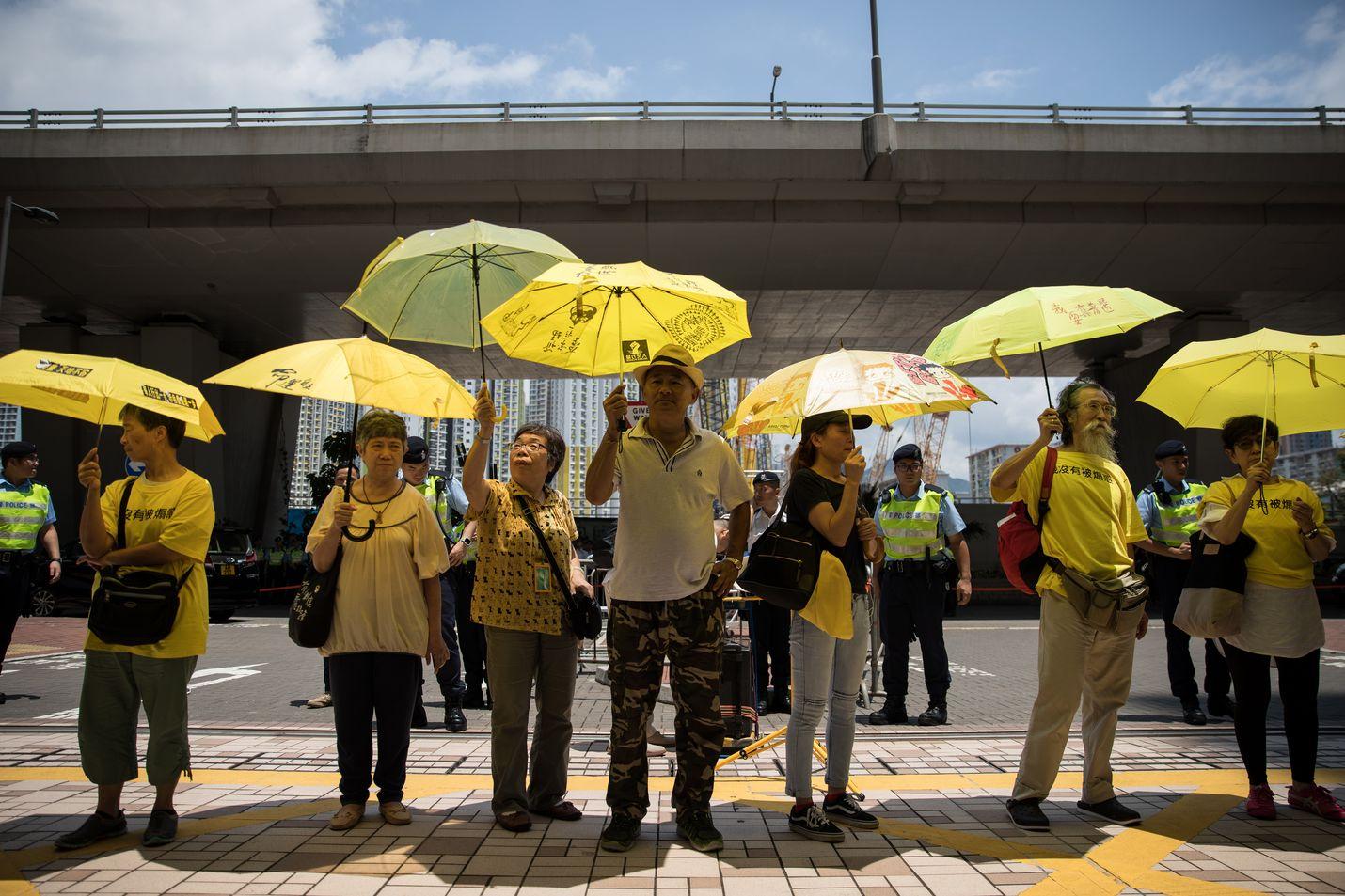 Sadat Occupy Central -johtajien kannattajat osoittivat mieltään oikeustalon edustalla keltaiseen pukeutuneina.