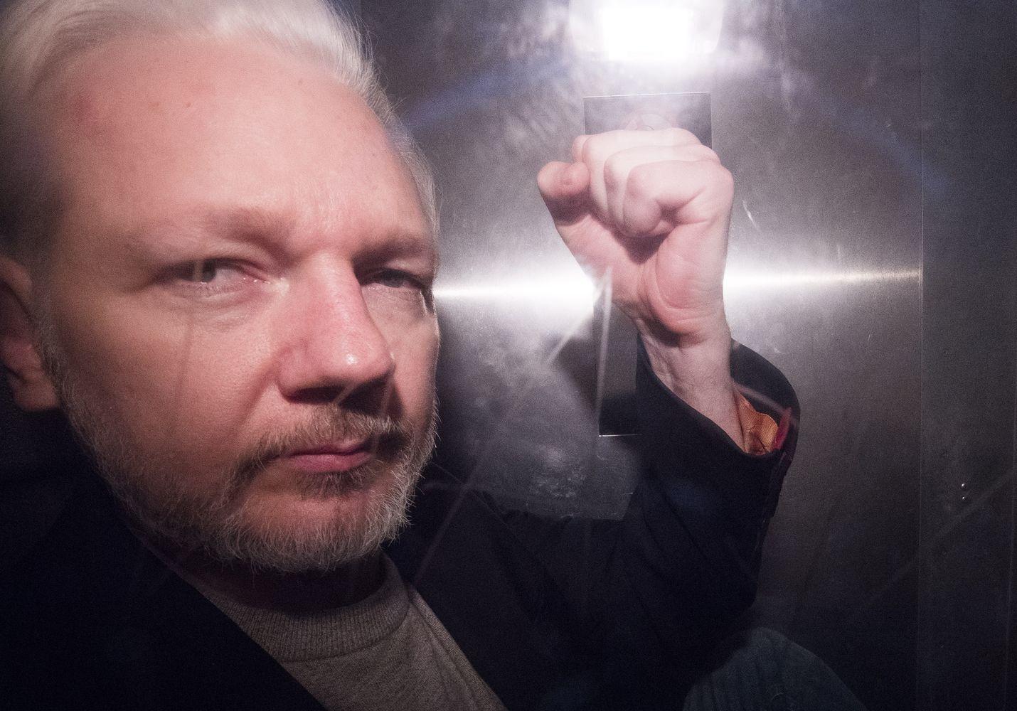 Julian Assange elehti poliisiauton lasin takaa valokuvaajille saatuaan 50 viikon vankeustuomion huhtikuussa Lontoossa.