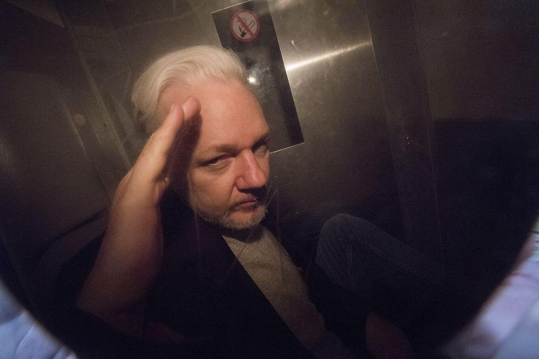 Julian Assange elehti poliisiauton lasin takaa valokuvaajille huhtikuussa Lontoossa.