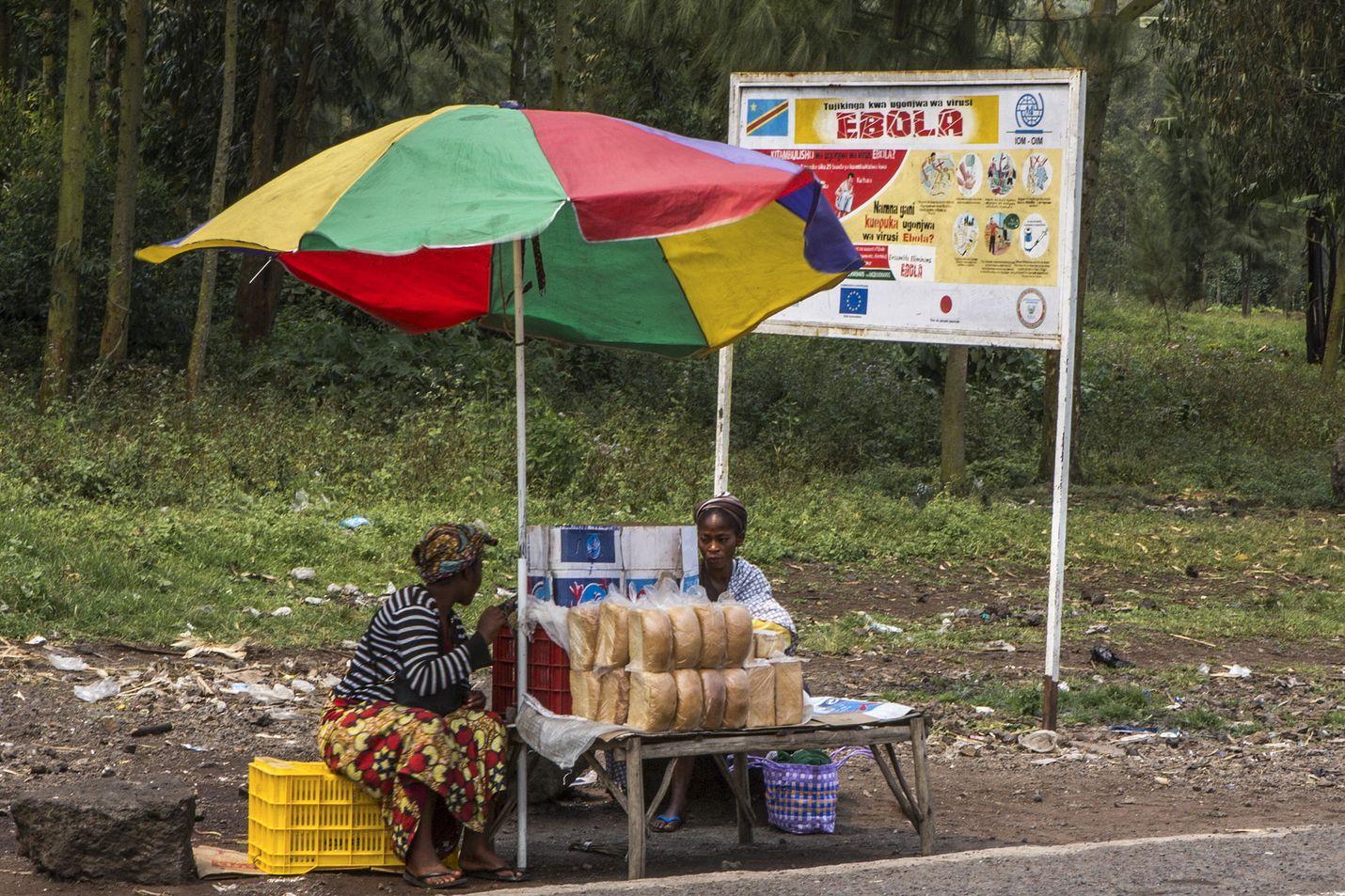 Katukauppiaat pystyttivät kojunsa ebolasta varoittavan kyltin eteen Goman ja Butembon välisellä maantiellä tiistaina.