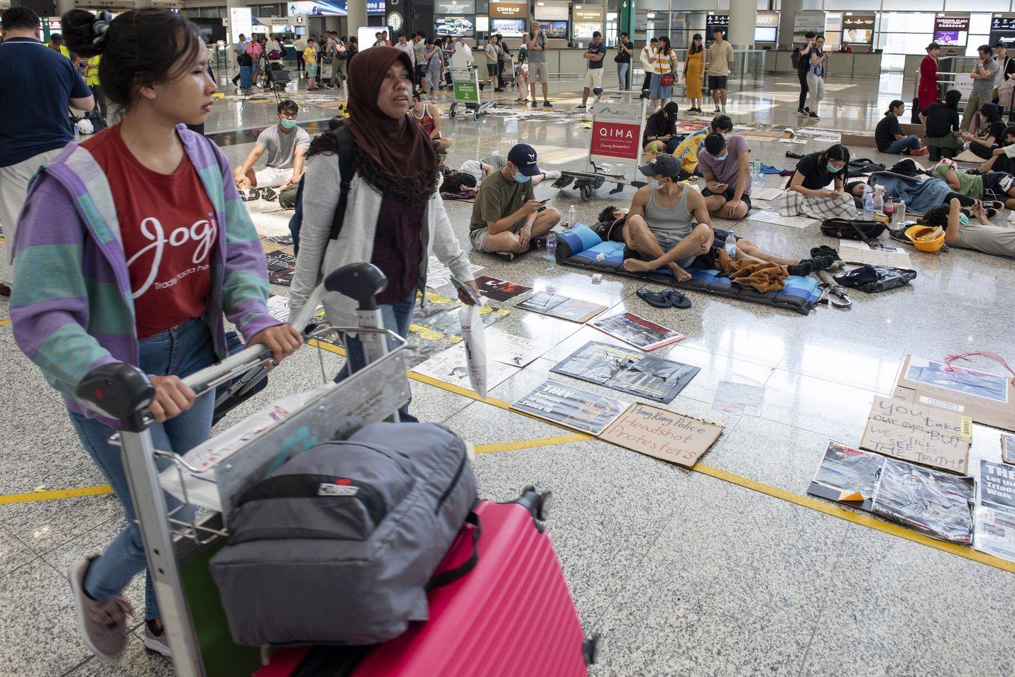 Matkustajat kävelivät hallitusta vastaan mieltään osoittavien ohi Hongkongin lentoasemalla keskiviikkona. Lennot lähtevät jälleen lentoasemalta kahden päivän väkivaltaisten protestien jälkeen.
