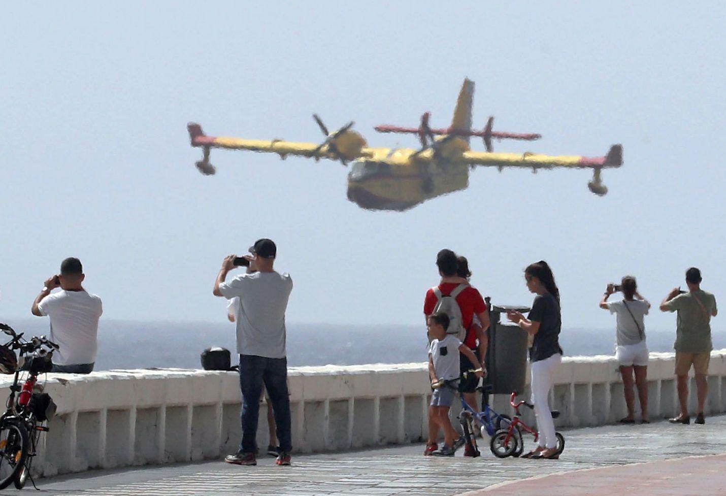 Turistit katselivat Las Palmasin rantapromenadilla kun sammutuslentokone valmistautuu ottamaan vettä merestä maastopalon raivotessa Gran Canarian keskiosissa sunnuntaina.
