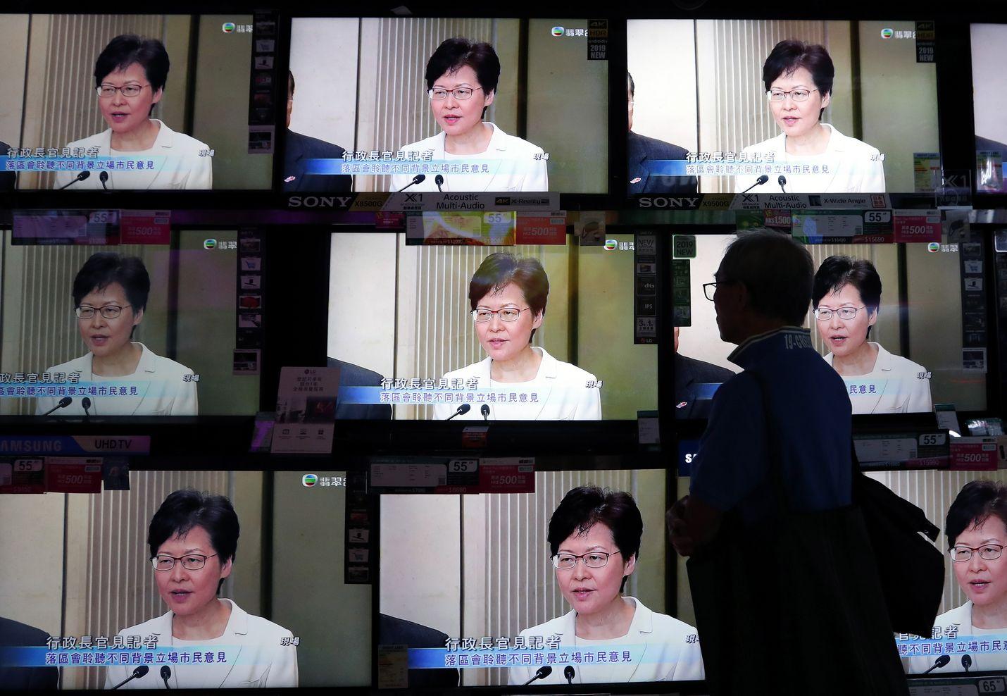 Hongkongilainen mies katseli kadulla televisiosta, kun hallintojohtaja Carrie Lam piti tiedotustilaisuutta torstaina kiistellyn luovutuslain kohtalosta.