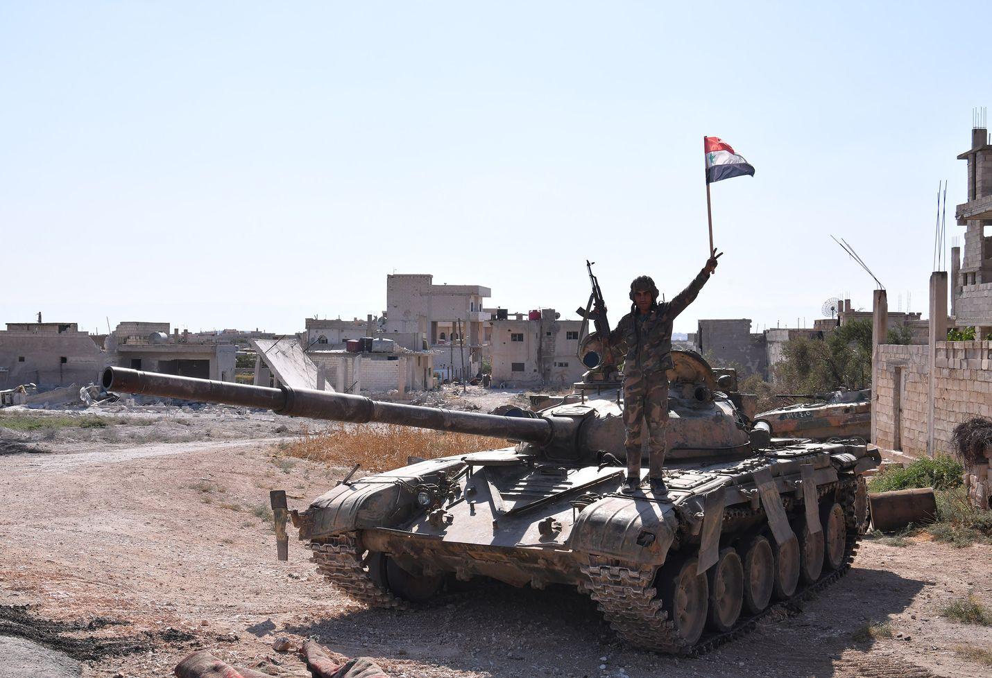 Syyrialainen sotilas heilutti maansa lippua panssarivaunun päällä Luoteis-Syyrian Khan Sheikhounin kaupungissa elokuun lopulla.
