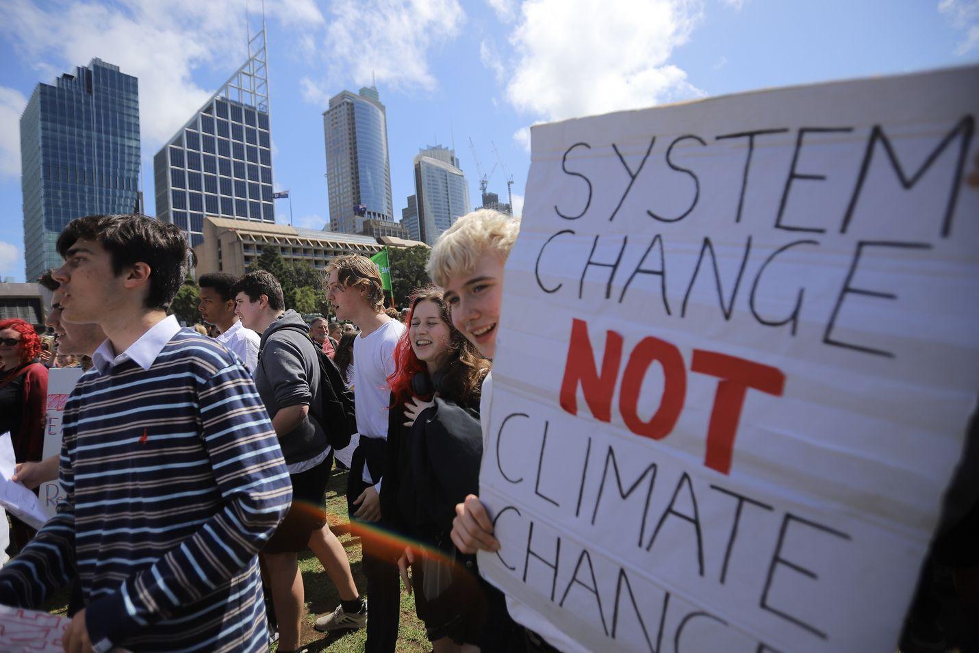"""""""Järjestelmän muutos, ei ilmaston muutos"""" lukee nuorten mielenosoittajien julisteessa ilmastoprotestin aikana Australian Sydneyssä perjantaina."""
