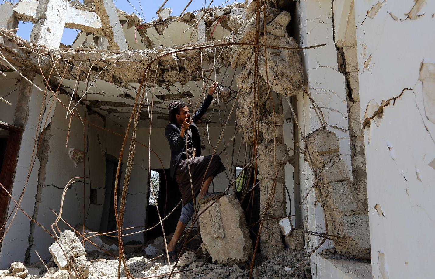 Jemeniläinen mies tutkii Saudi-Arabian johtamassa ilmaiskussa tuhottua taloa Sanaassa torstaina.