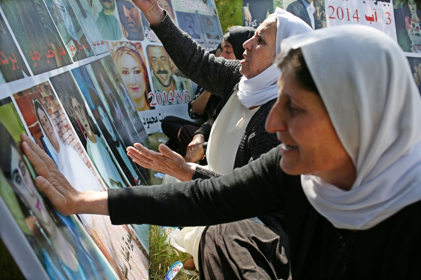 Jesidi-naiset osoittavat surua katsellessaan jesidien kansanmurhassa kuolleiden omaistensa kuvia Irakin kurdialueella Baadressa elokuussa 2019. Uusi Isis-johtaja oli keskeisenä vaikuttamassa jesidien vainoihin.