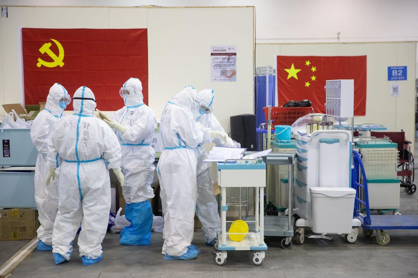 Terveydenhuollon työntekijöitä Wuhaniin koronavirukseen sairastuneiden hoitoa varten rakennetussa sairaalassa.