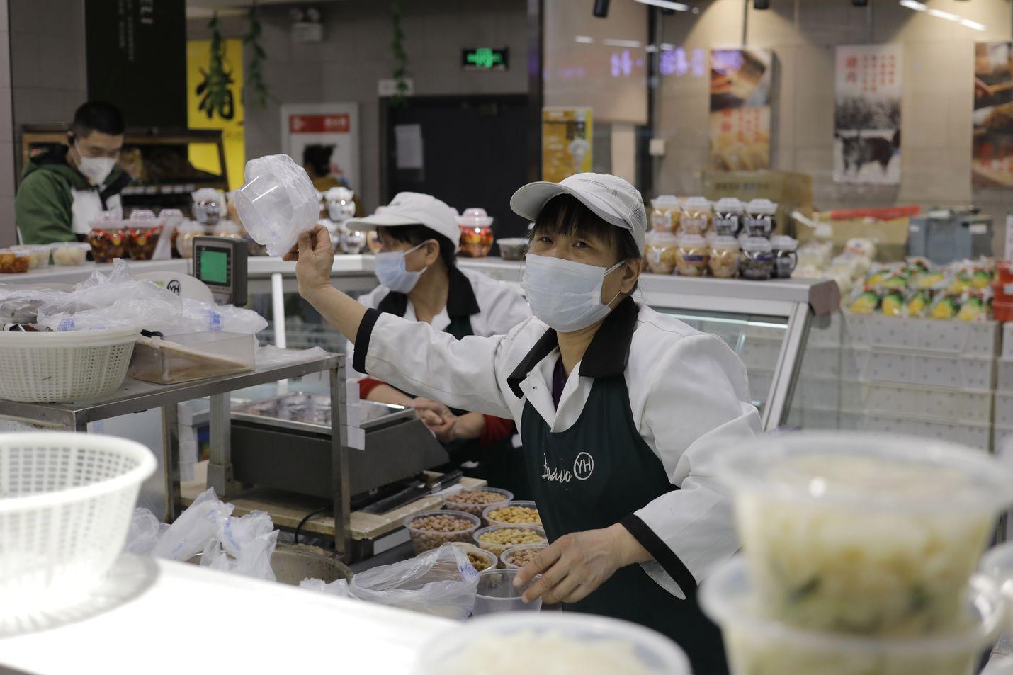 Myyjällä oli kasvoillaan suojamaski kun hän työskenteli Pekingissä sijaitsevassa supermarketissa tiistaina. Maanantaina ei Kiinassa raportoitu enää uusista paikallisesti levinneistä koronavirustartunnoista Hubein maakunnan ulkopuolella.