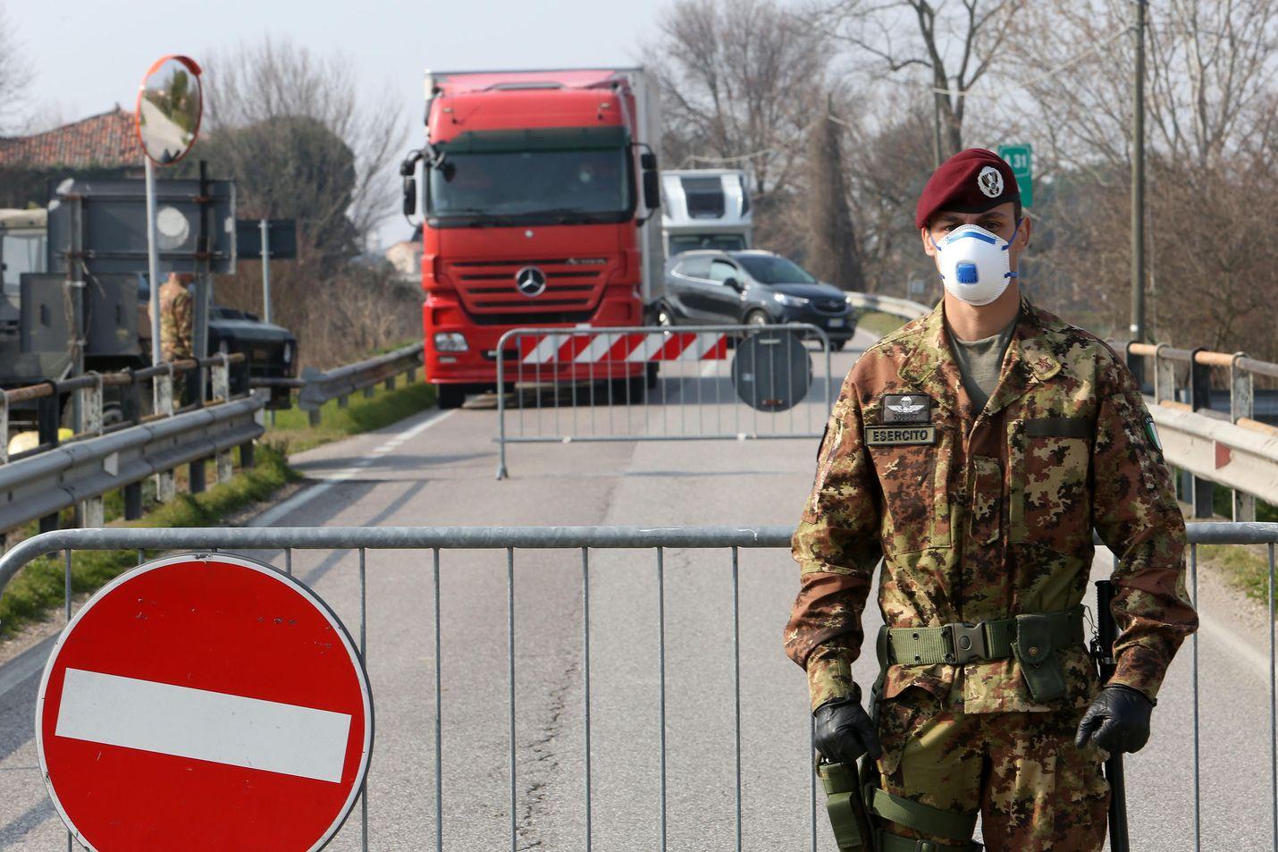 Tämä voi olla pian tuttu näky myös Uudenmaan rajoilla. Sotilas valvoo koronan vuoksi eristetyn alueen liikennettä Padovan lähellä Pohjois-Italiassa.