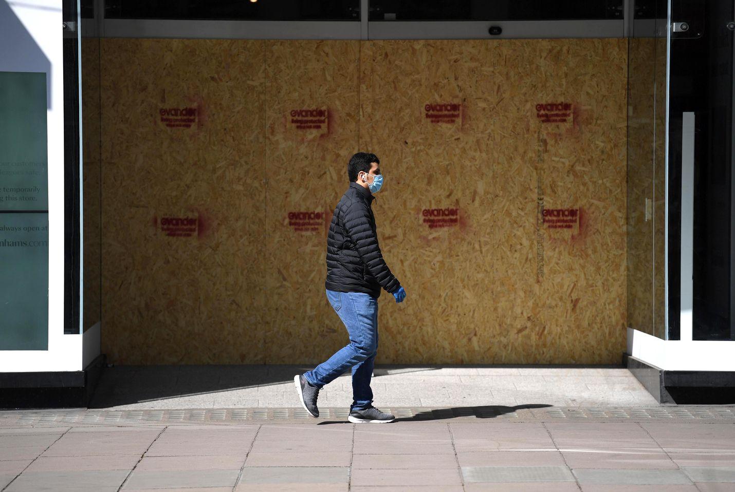 Kasvosuojaan pukeutunut mies ohittaa suljetun liikkeen tunnetulla kauppakadulla Oxford Streetillä Lontoossa. Britanniassa koronaviruskuolemien määrä voi olla tuhansia arvioitua korkeampi.