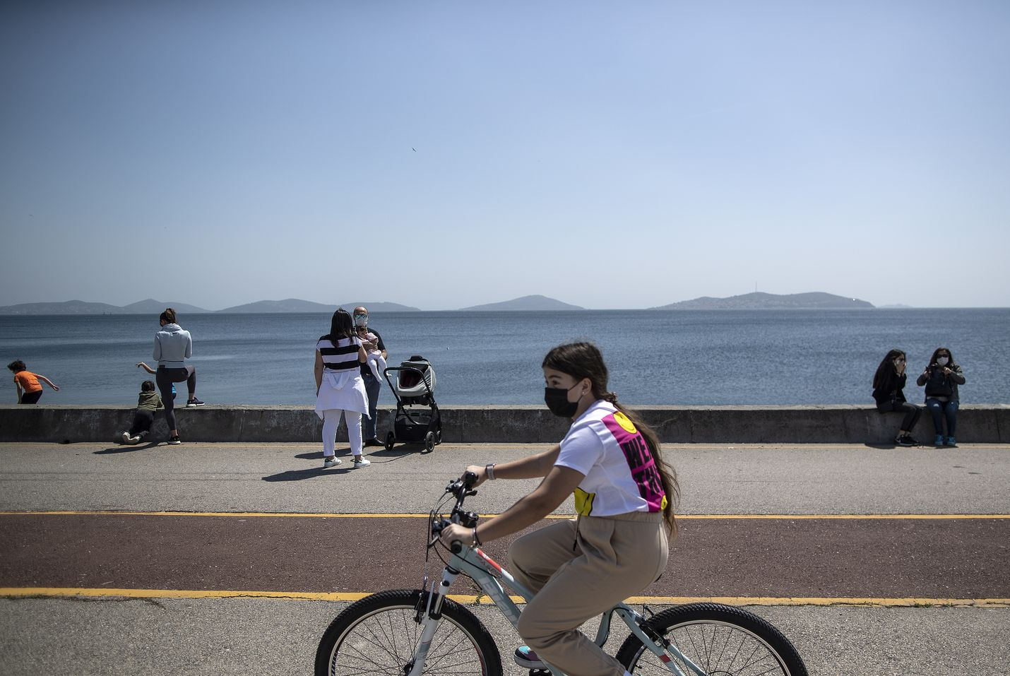 Maskia käyttävä lapsi pyöräili puistossa Istanbulissa Turkissa 13. toukokuuta.