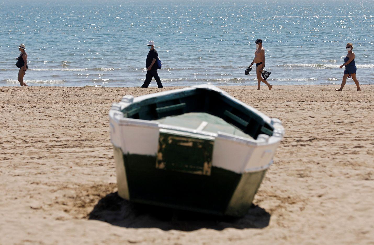 Ihmiset huolehtivat etäisyyden säilyttämisestä Malvarrosan rannalla Espanjan Valenciassa perjantaina.