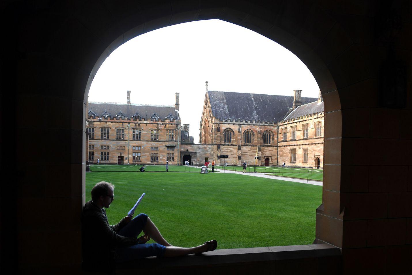 Opiskelija lukee lehteä Sydneyn yliopistolla Australiassa. Hallitus haluaa, että opiskeluala vaikuttaisi jatkossa lukuvuosimaksun suuruuteen.