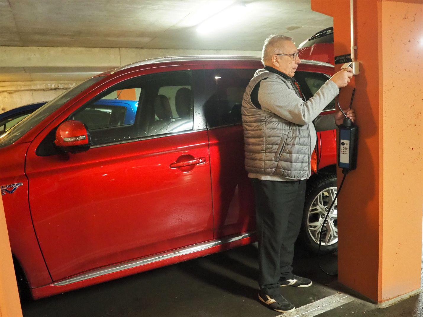 """Mitsubishi-hybridin ajoakku latautuu täyteen yön aikana Jorma Moision kotitalon parkkihallissa. Ajossa auto vaihtaa sähkölle heti, kun nopeus laskee alle 65 kilometrin, mutta sähköä voi myös """"säilöä"""" kaupunkiosuuksille."""