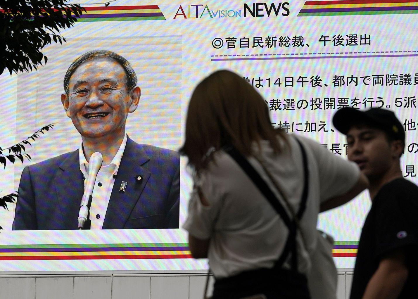 Uutistaulut Tokion katukuvassa kertoivat maanantaina Yoshihide Sugan voittaneen äänestyksen valtapuolueen puheenjohtajuudesta.