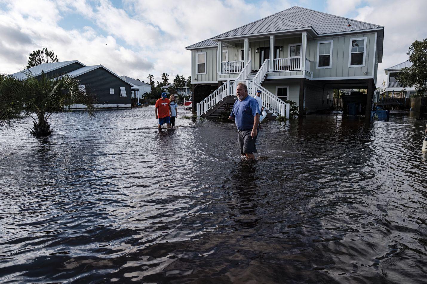 Ihmiset kävelivät läpi tulvivan naapuruston keskiviikkona Orange Beachin alueella Yhdysvaltojen Alabamassa.