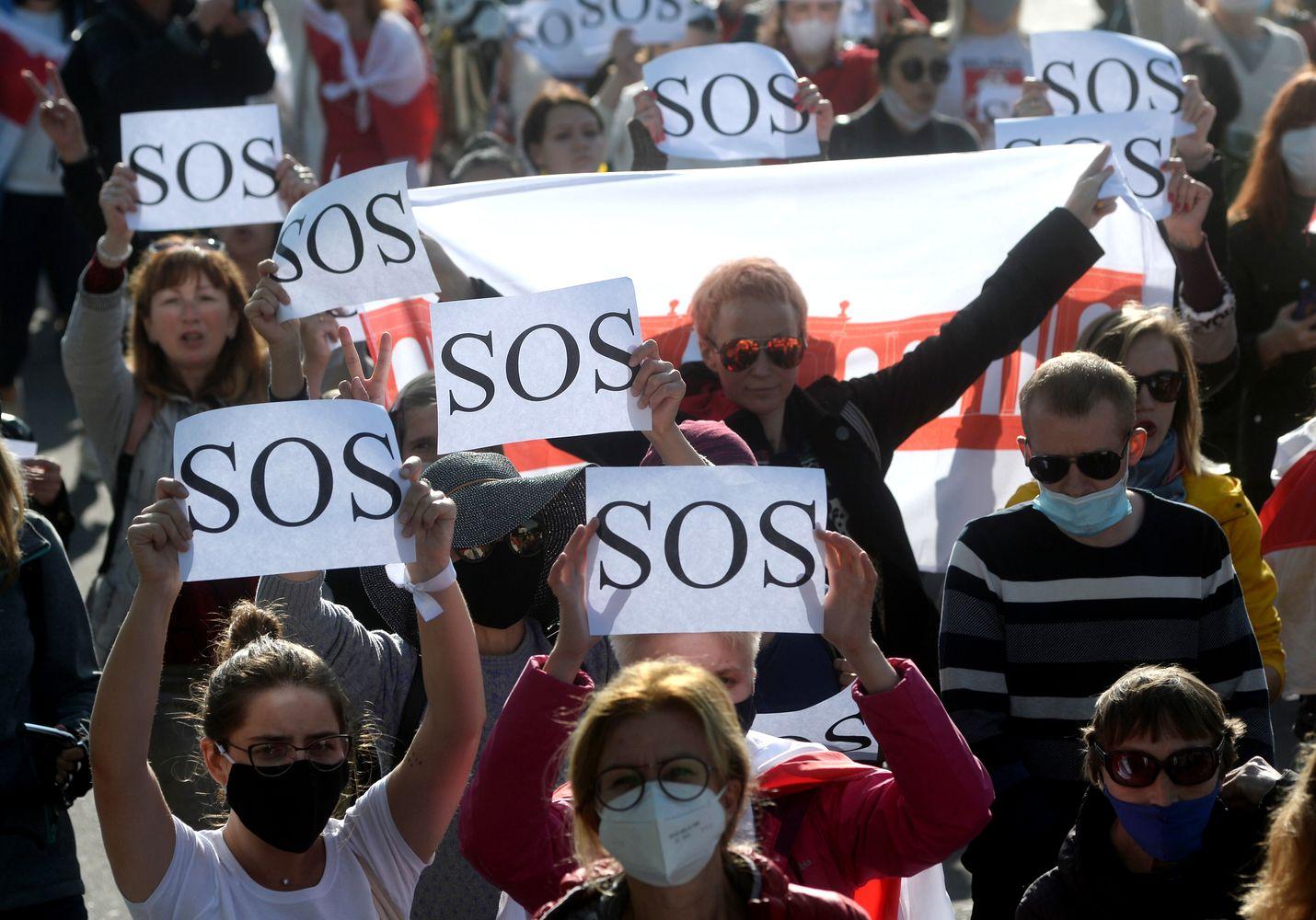 Naiset kantoivat SOS-kylttejä lauantaina Minskissä järjestetyssä protestissa. Satoja osallistujia pidätettiin.