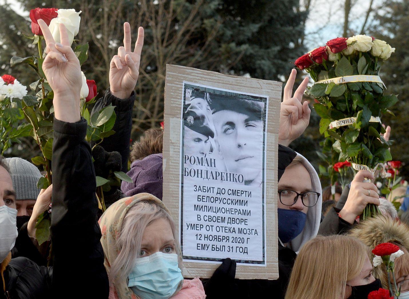 Surmatun mielenosoittajan hautajaisissa näytettiin voitonmerkkejä ja kukkasia minskiläisen kirkon ulkopuolella perjantaina.