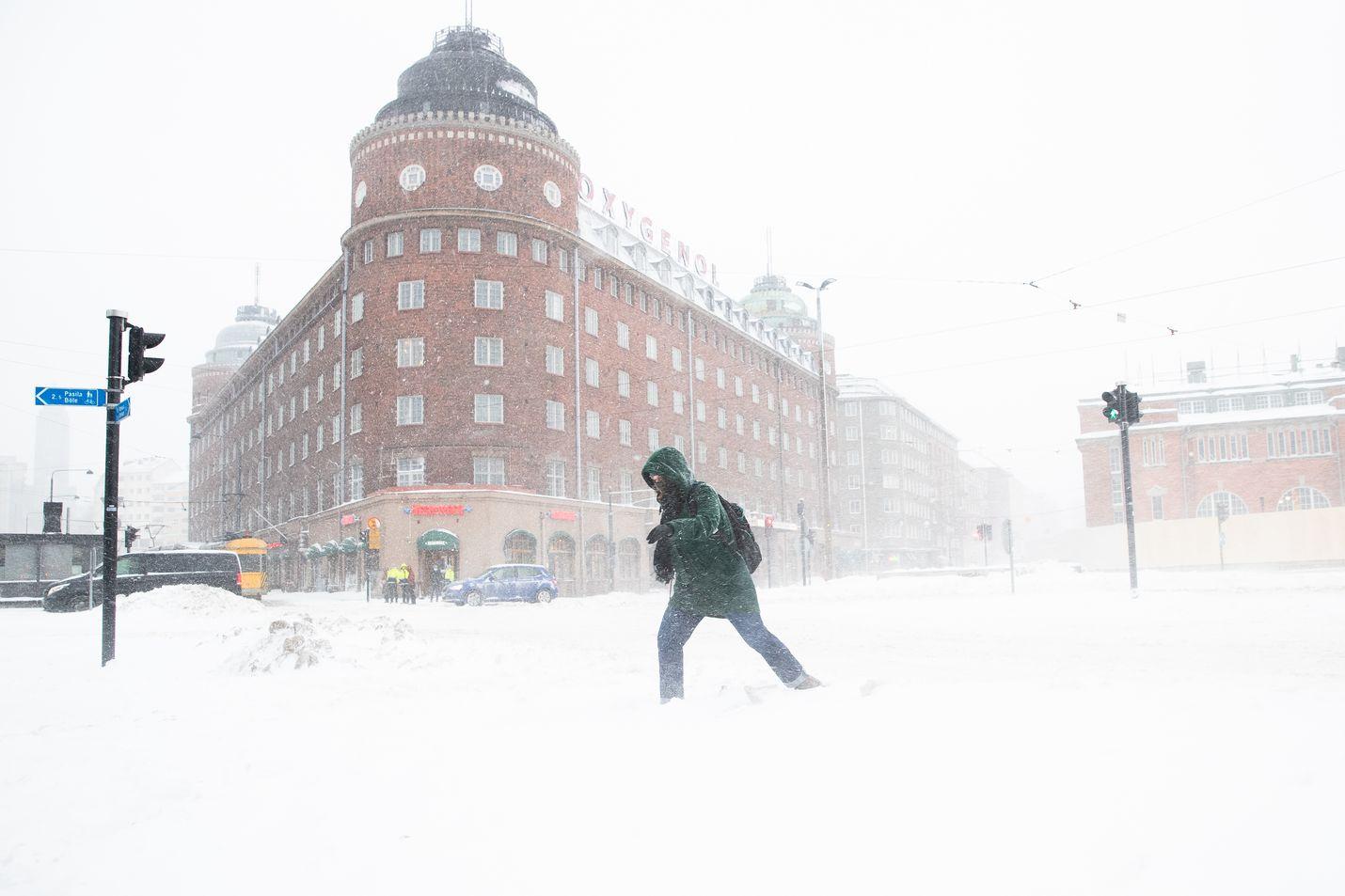 Jalankulkija taivaltaa läpi tuulen ja tuiskun Helsingissä.