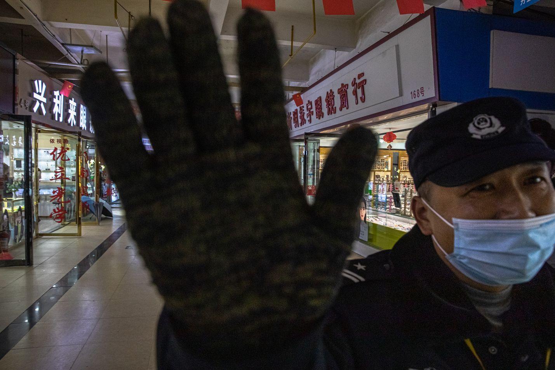 Vartija yritti estää valokuvaajaa kuvaamasta Huananin kalatoria Kiinan Wuhanissa viime joulukuussa. Koronaviruksen alkuperä jäljitettiin yli vuosi sitten sinne.