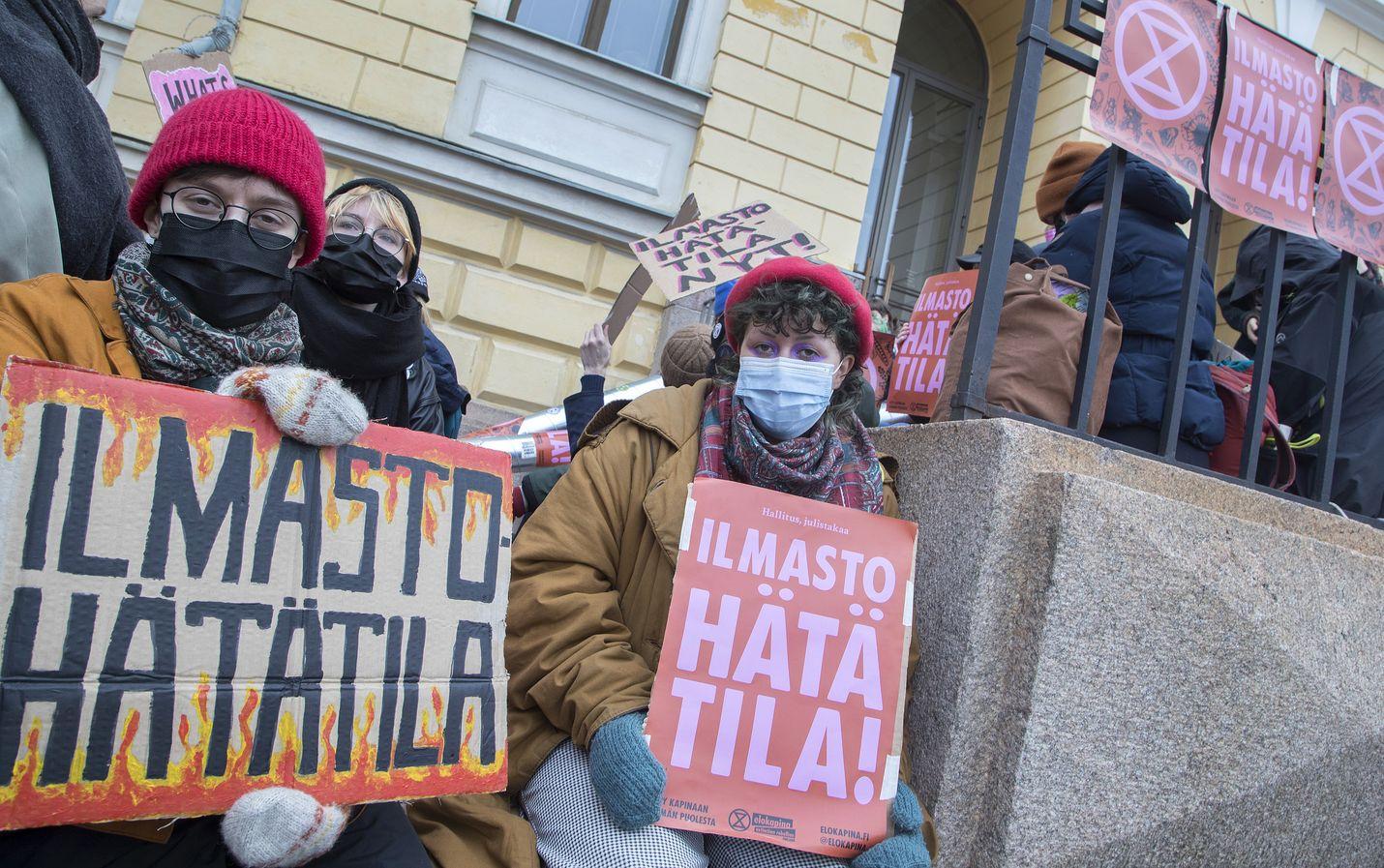 Veera Leno (oikealla) ja Saga Kampman vaativat ilmastohätätilan julistamista perjantaina Valtioneuvoston ovien edustalla.