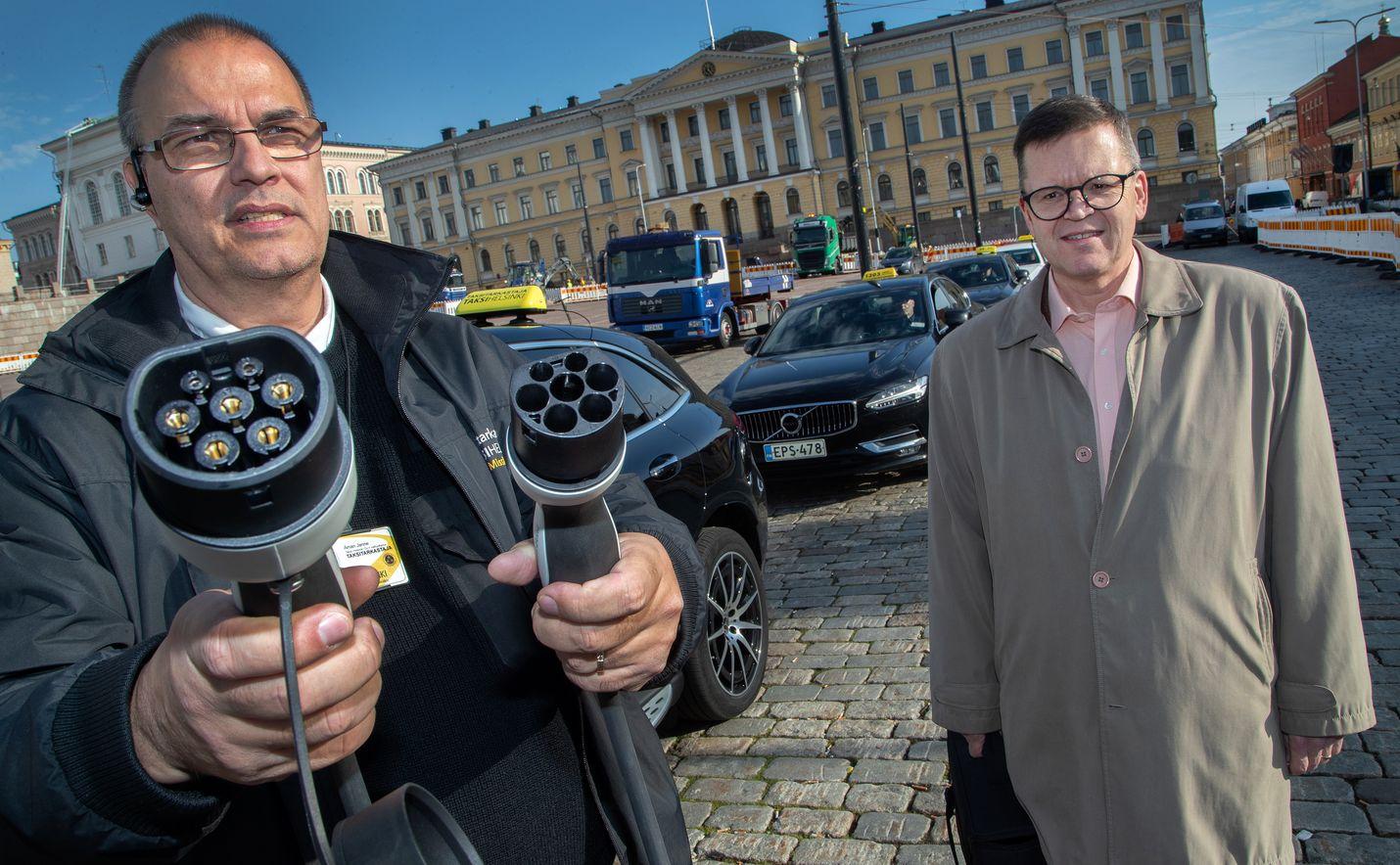 Taksi Helsingin taksitarkastajan Janne Åmanin tarkastajanauto kulkee sähköllä. Vieressä Senaatintorilla on Taksiliiton toimitusjohtaja Timo Koskinen. Taksialan sähköistymistä vauhdittaa myös uusi laki.