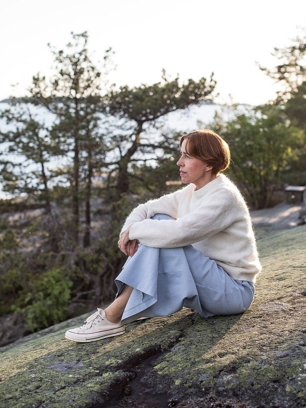 Virpi Suutari istuu kalliolla