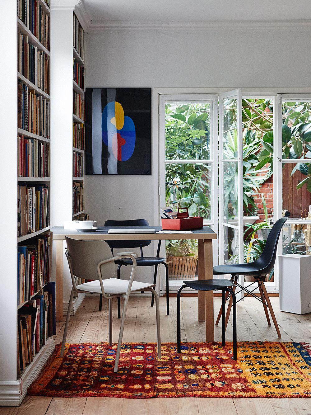 Artekin Lukki-tuoli ja Vitran Eames DSW -tuoli pöydän ääressä.