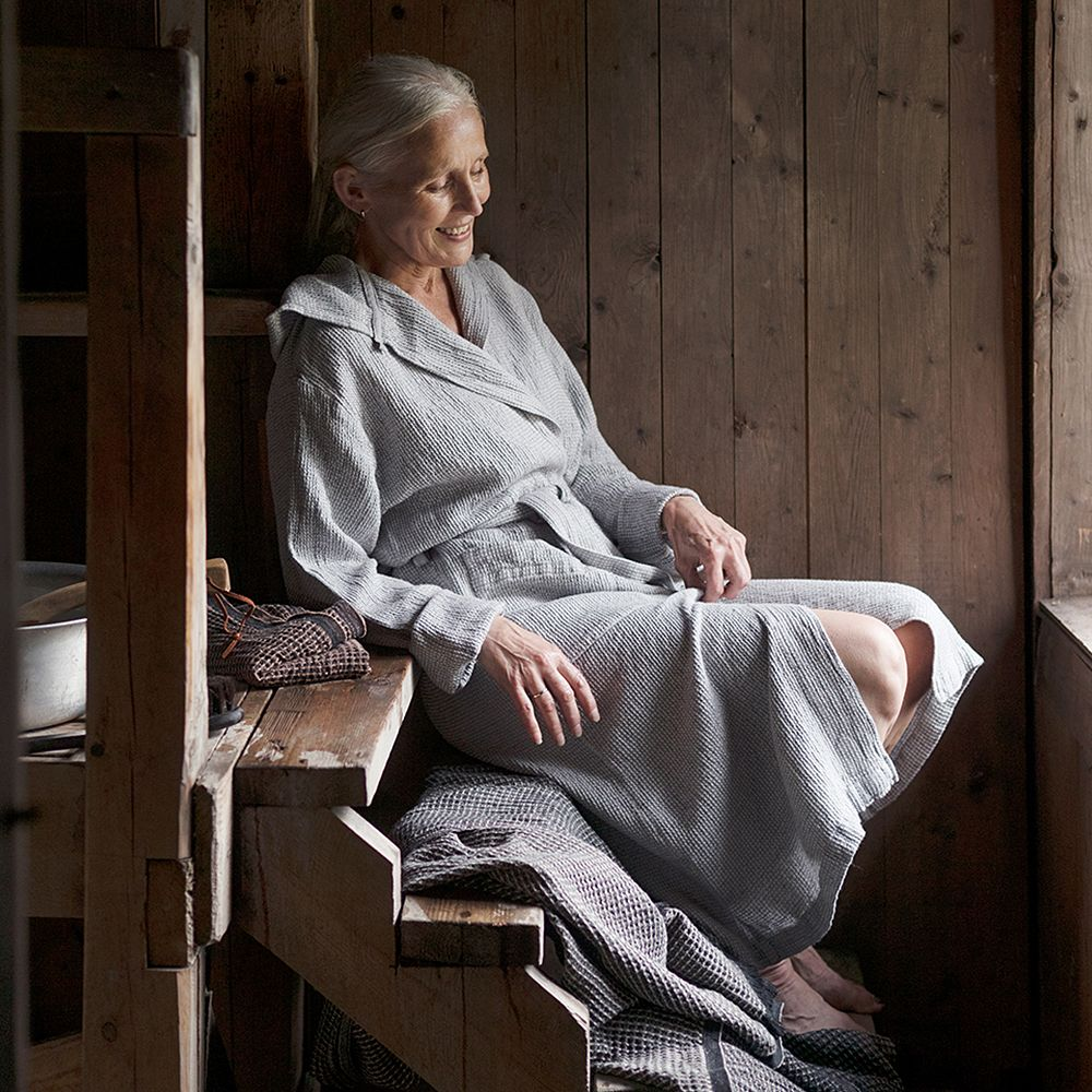 A woman sitting in a sauna wearing the Terva bathrobe by Lapuan Kankurit.
