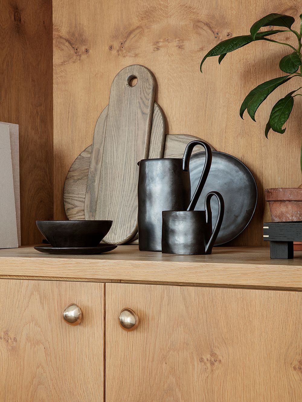 Ferm Living's Flow tableware placed on a sideboard.