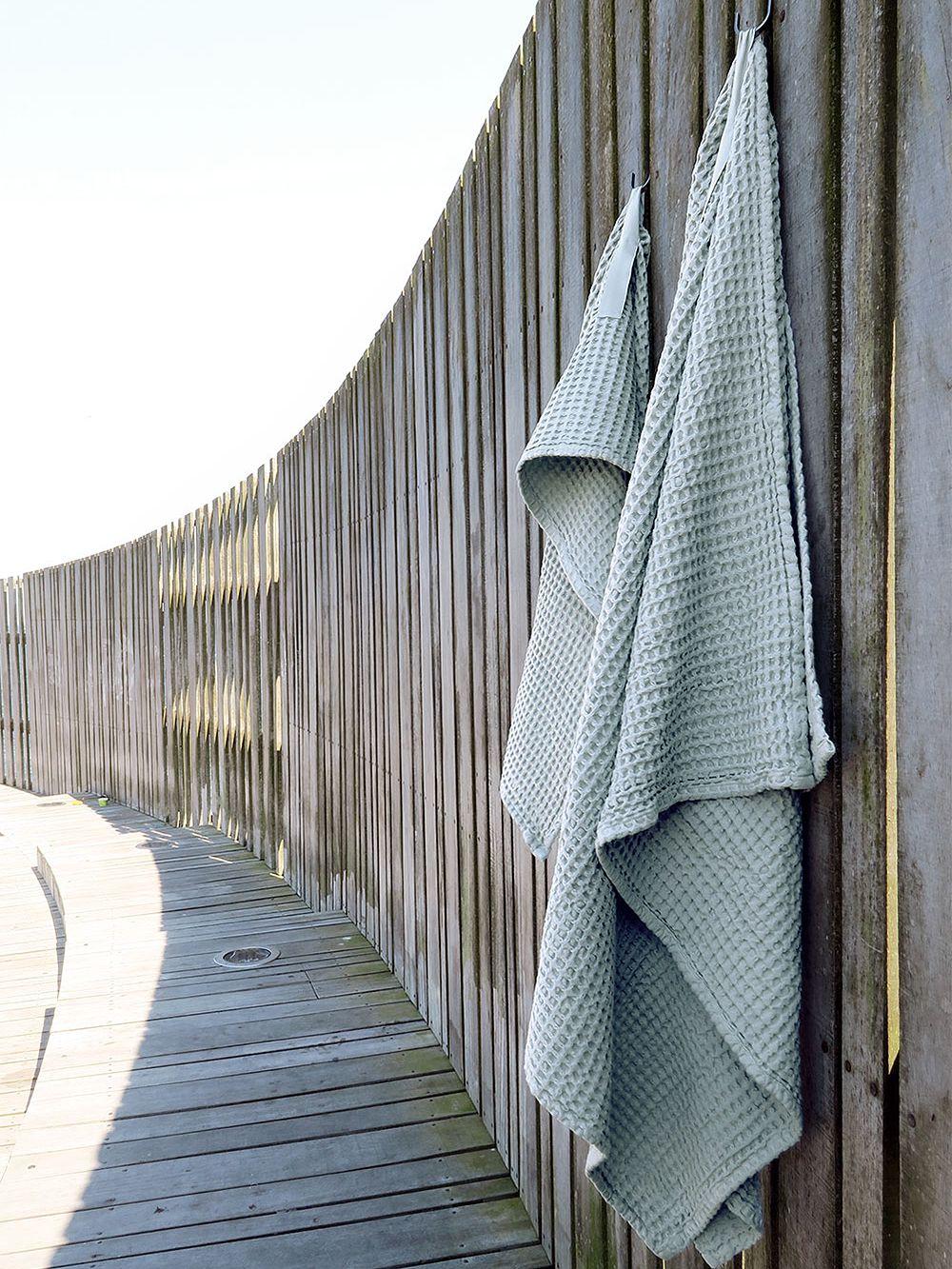 The Organic Company's Big Waffle giant towel hung on a fence.
