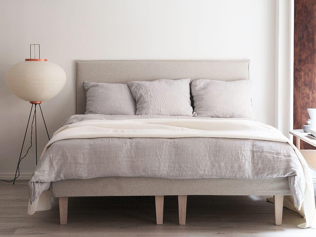 Vitran Akari 10A -lattiavalaisin makuuhuoneessa. Sängyssä Matrin Slim-sängynpääty ja pellavaiset vuodevaatteet.