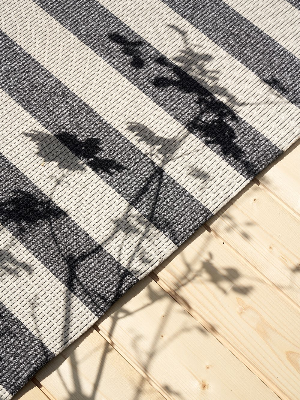 Big Stripe rug by Woodnotes against a wooden floor.