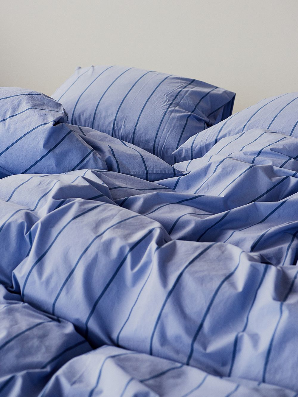 Tekla's striped duvet covers and pillow shams on a bed.