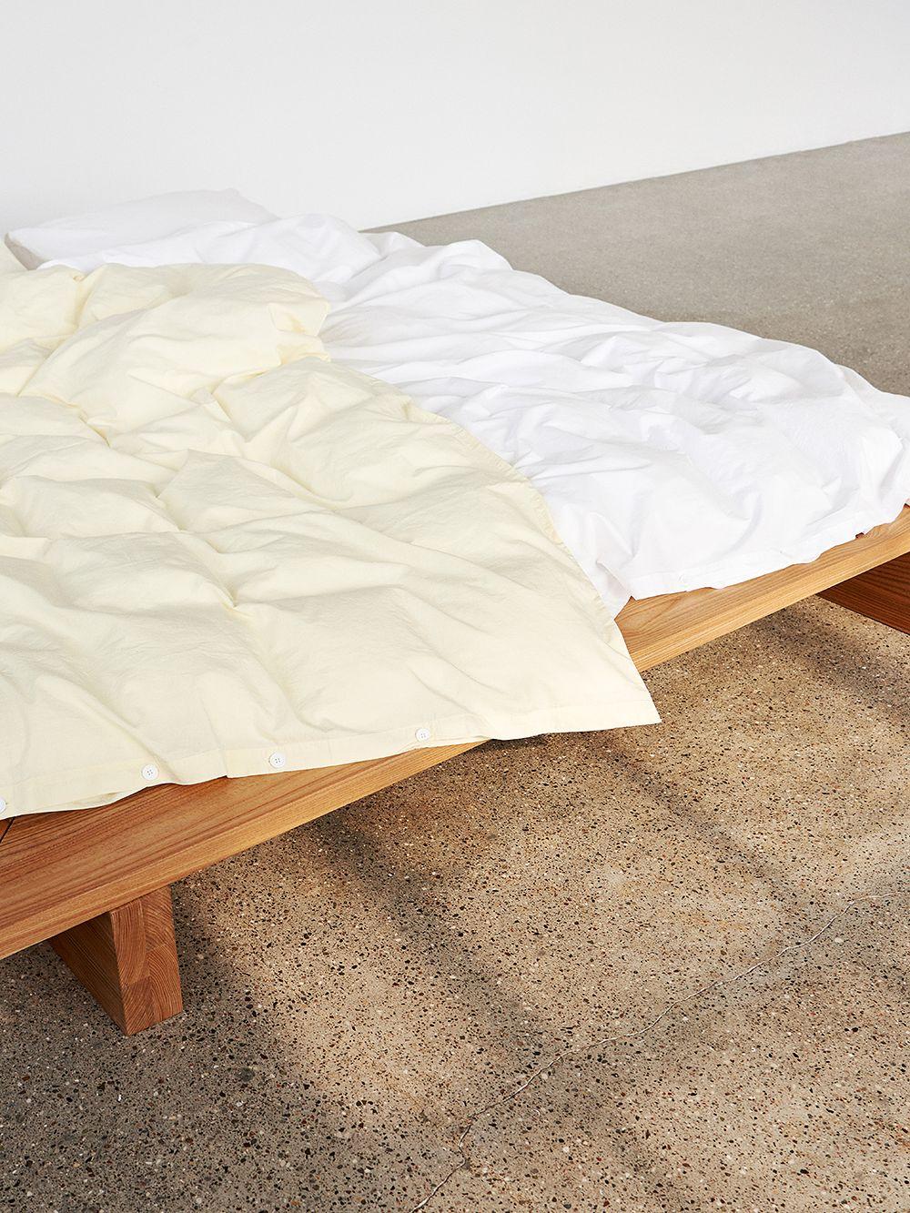 Teklan vaaleankeltainen ja valkoinen pussilakana sängyllä.