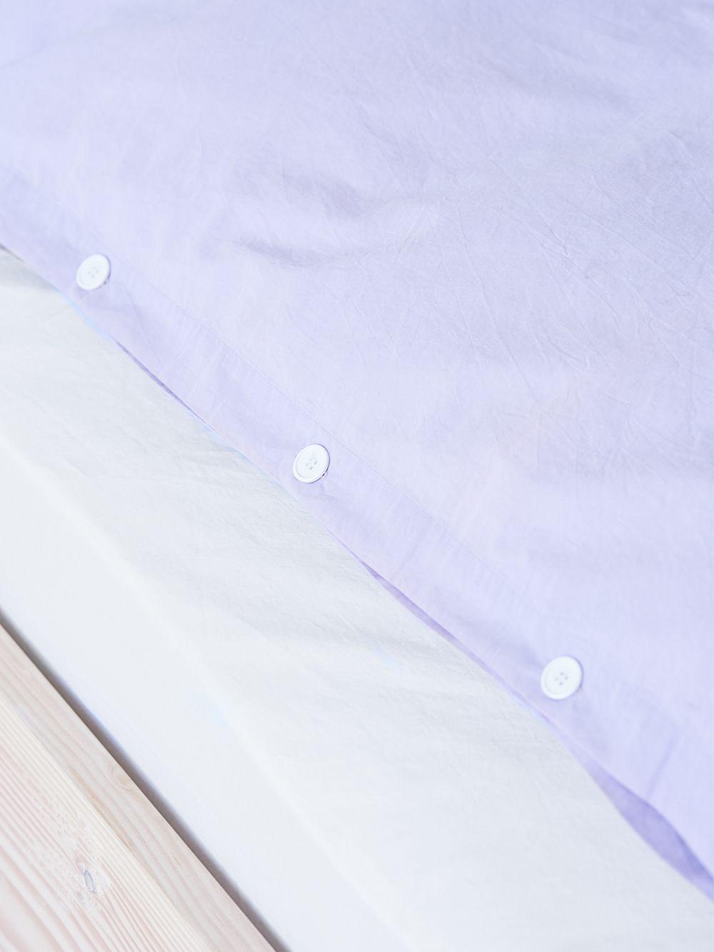 Teklan laventelin värinen pussilakana lähikuvassa.