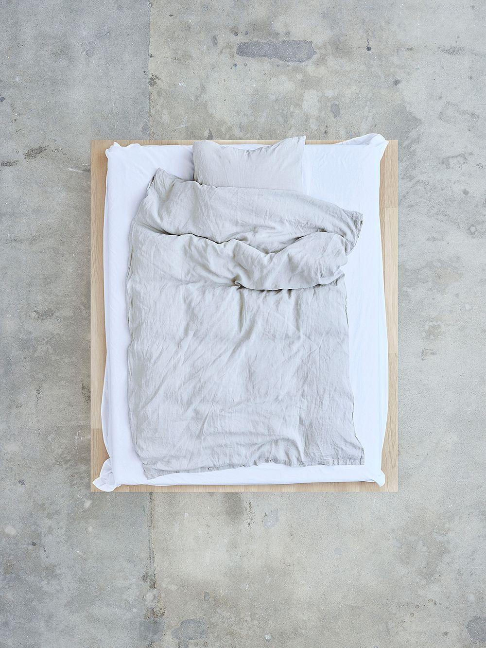 Teklan vaaleanharmaa pussilakana ja tyynyliina pedattuna sänkyyn.