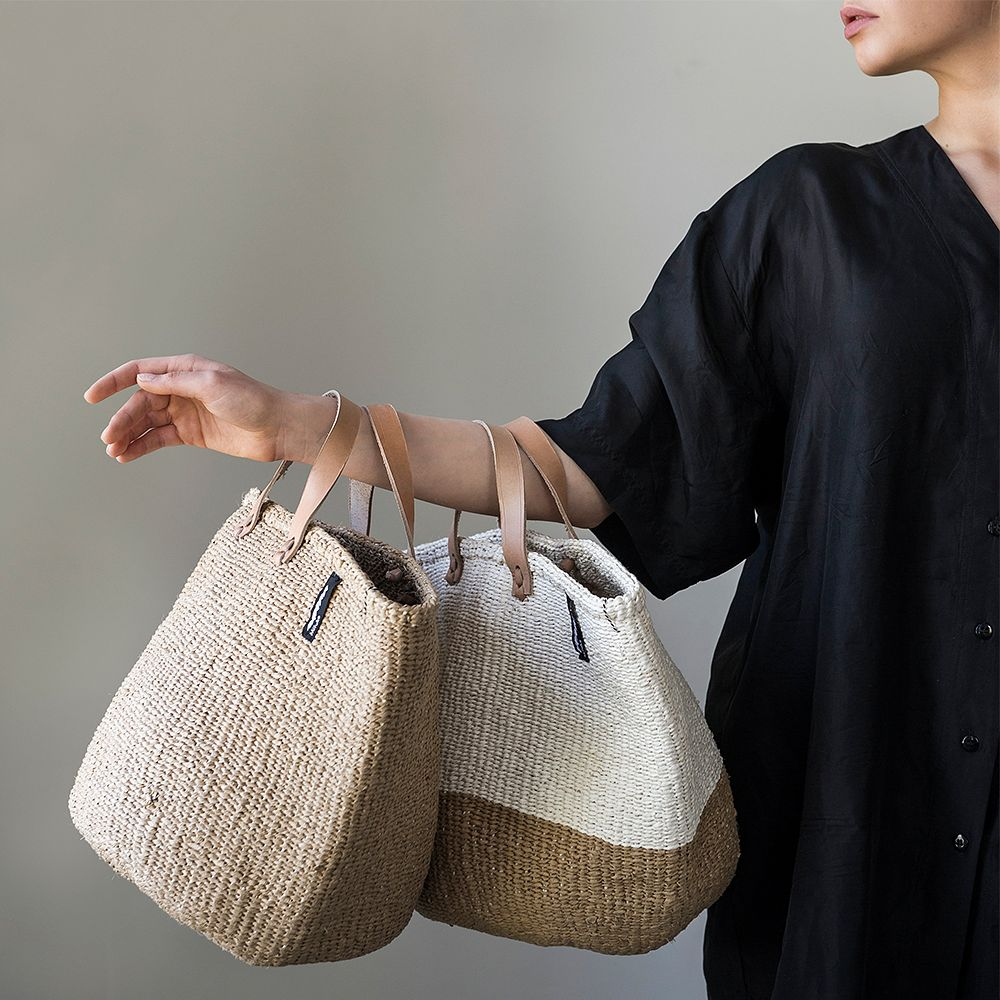 Mifuko's Kiondo baskets with handles, held by a woman.