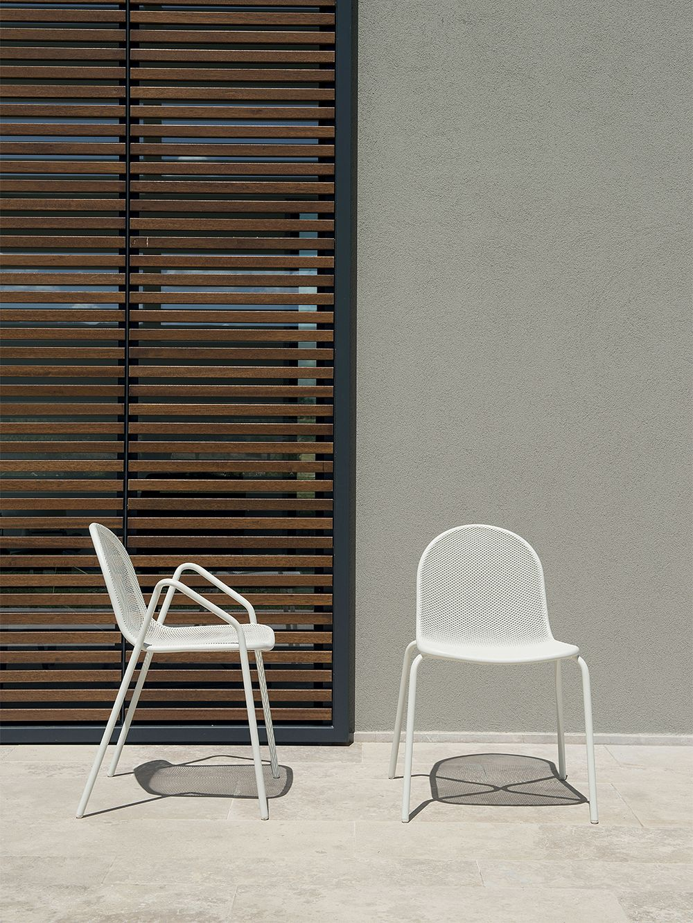 Emu's Nova armchair and chair outside.