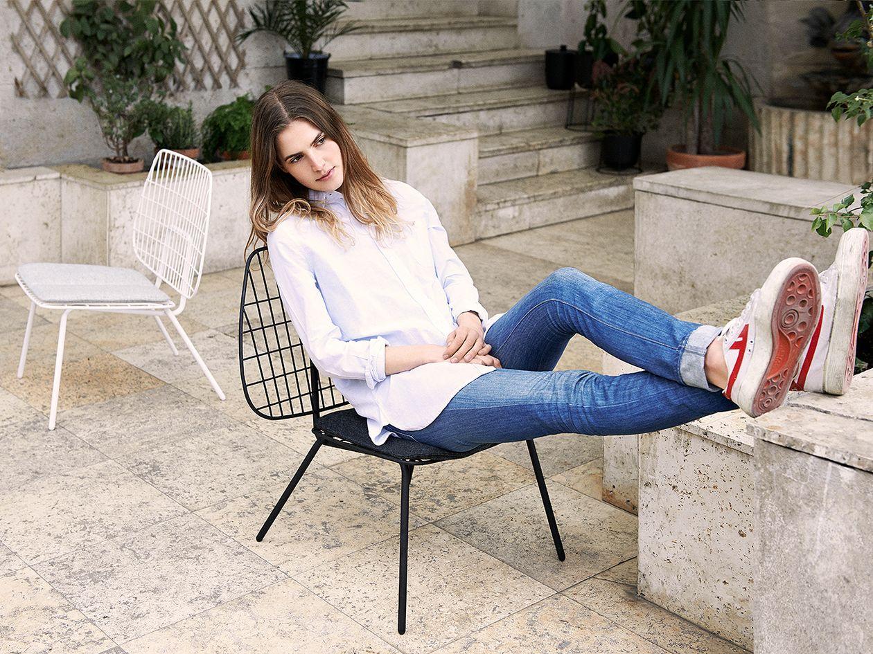 Nuori nainen istuu Menun WM String -nojatuolissa ulkona.