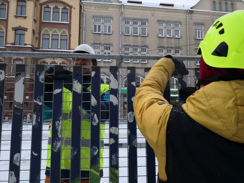 Taiteilijat Jaakko Himanen ja Vesa Toukomaa kiinnittämässä Ratikan väliaikaista taidetta työmaa-aitoihin.