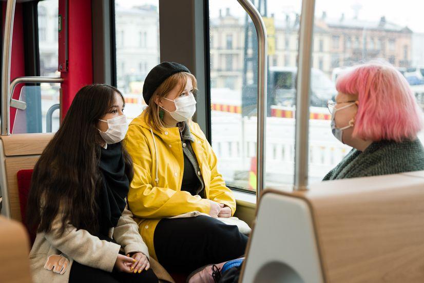 Kolme matkustajaa istumassa Ratikan kyydissä ja katsomassa ulos ikkunasta.