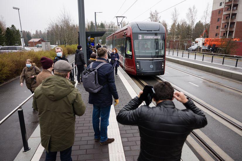 Matkustajia odottamassa ratikkapysäkillä vaunuun pääsyä.