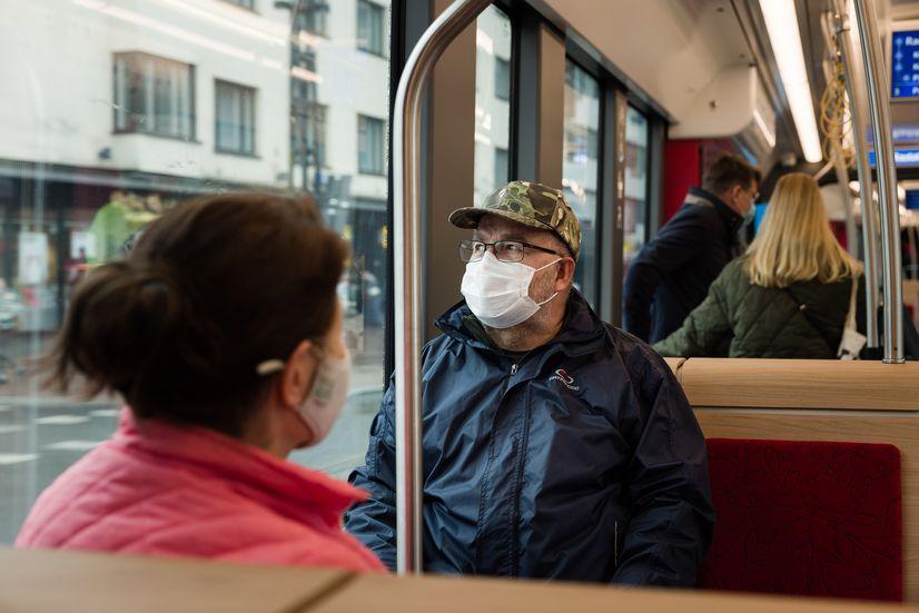 Matkustaja istumassa Ratikassa ja katsomassa ulos ikkunasta.