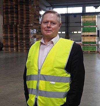 Kaukokiidon toimitusjohtaja seisoo logistiikkahallissa.