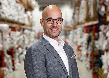 Daniel Ward, Eurokankaan toimitusjohtaja, seisoo ryhdikkäänä varastossa, jossa näkyy epätarkasti kangaspakkoja.