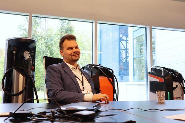 Kempowerin myyntijohtaja Tommi Liuska istuu pöydän ääressä, vierellään Kempowerin sähkölatureita.