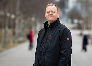 Layher Finlandin toimitusjohtaja Marko Mölsä seisoo Lahden keskustassa mustassa takissa.